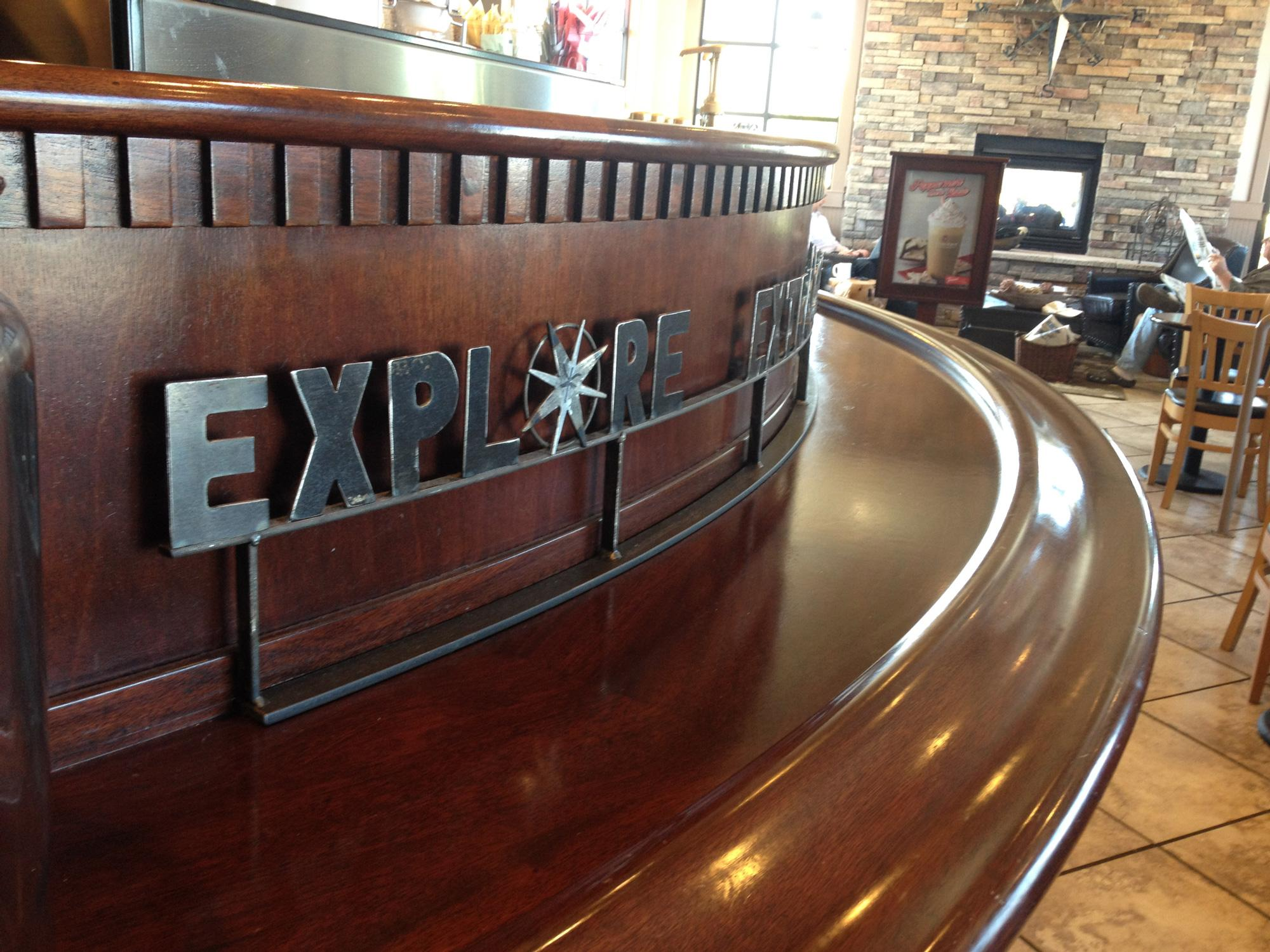 Metal Explore Extraordinary sign at flagship Lacey coffee shop