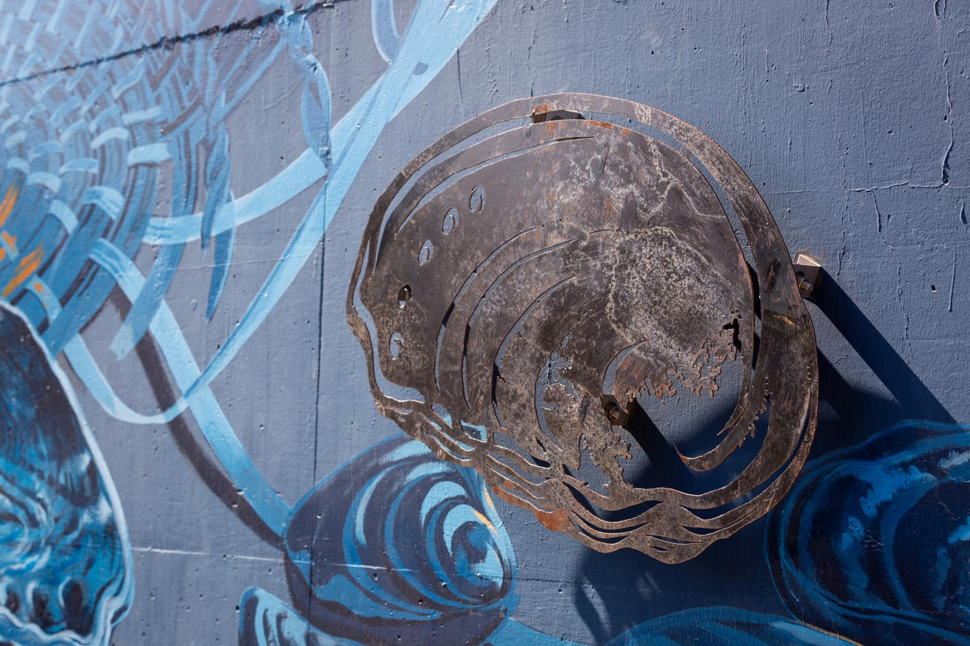 Metal cutout of an abolone shell installed against blue mural backdrop.
