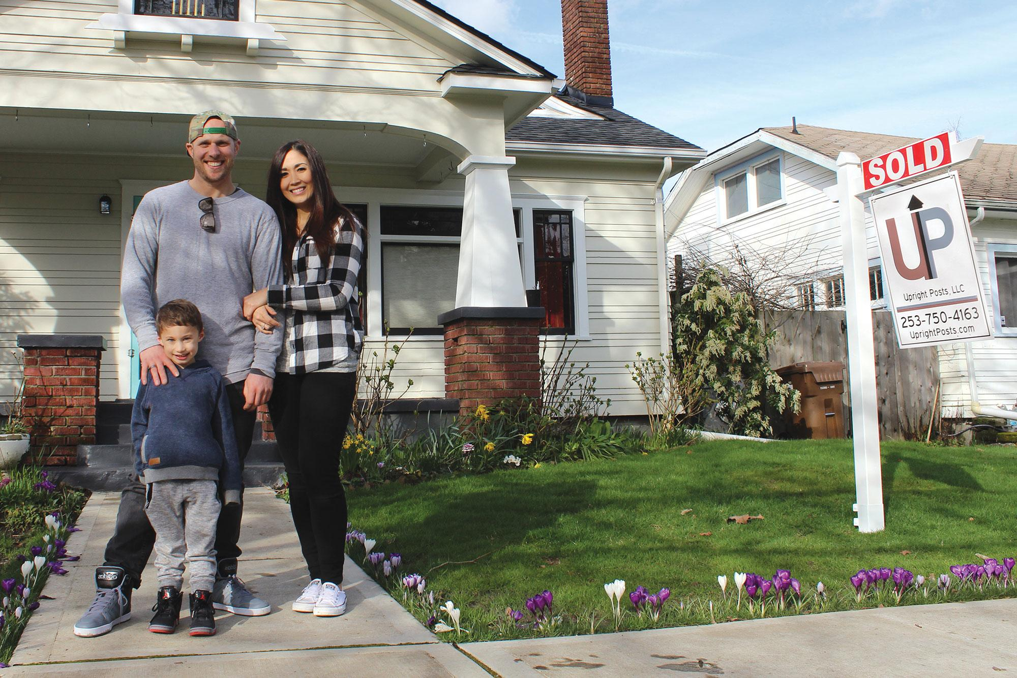 Family standing outside of a newly purchased home
