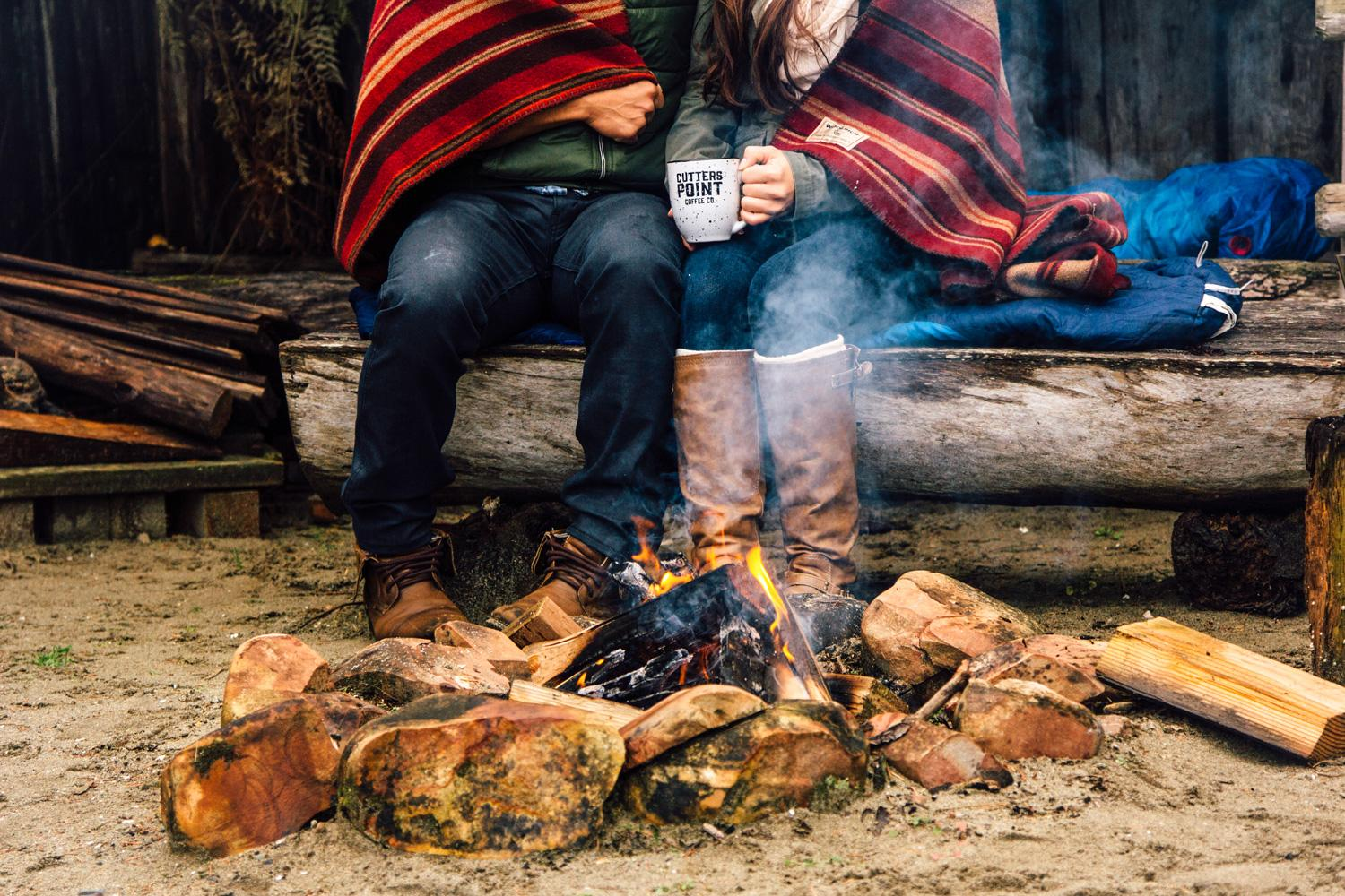 Couple drinking coffee by a fire