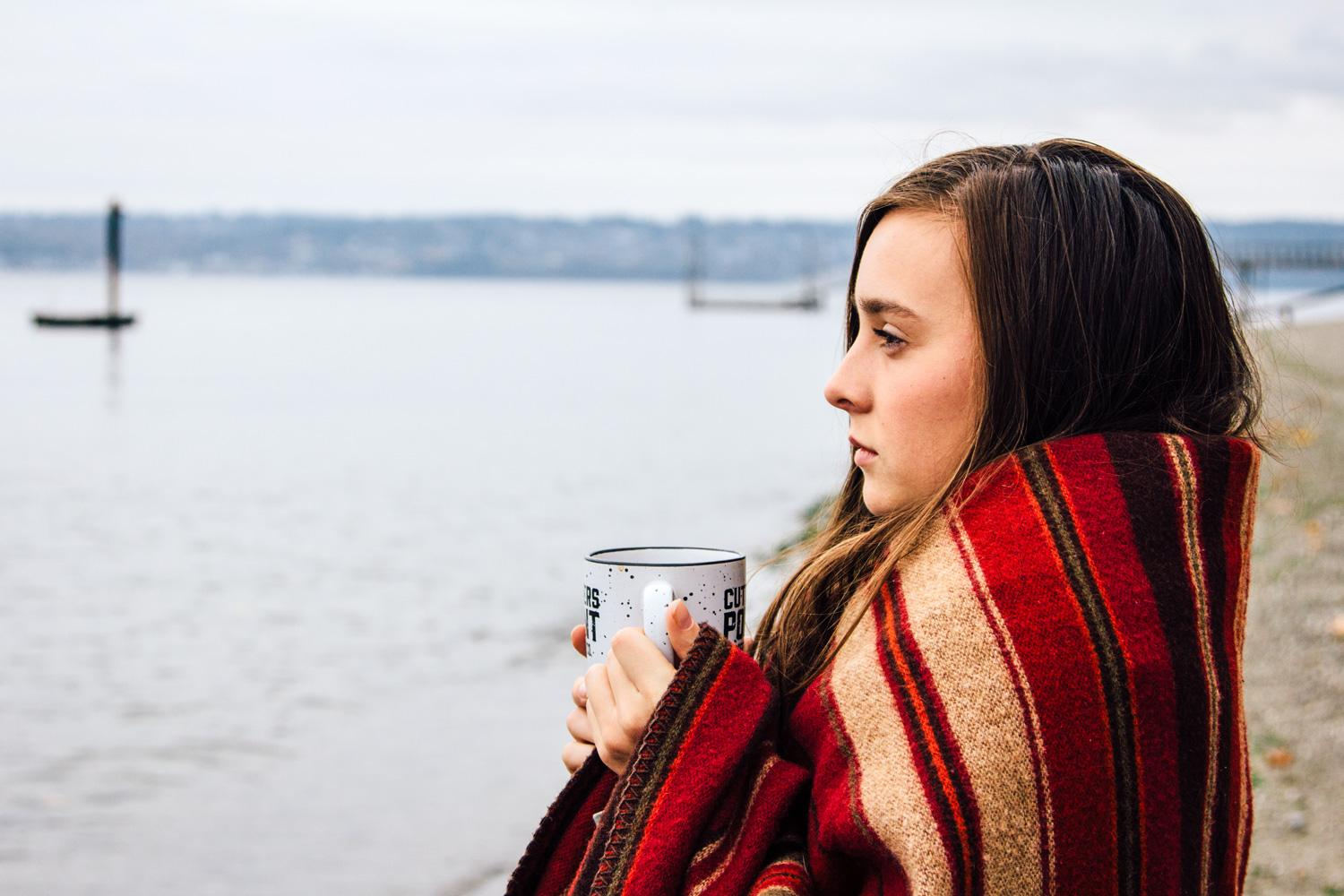 Young woman wrapped in a blanket looking at the Puget Sound